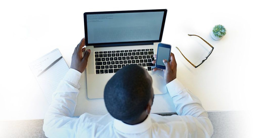 A man sitting in front of his laptop checking his mobile phone