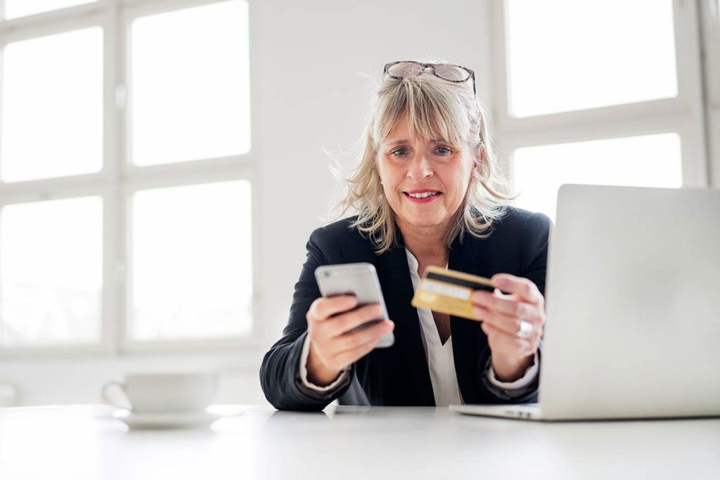A woman sitting in front of a laptop keeping a mobile phone and a credit card in her hands