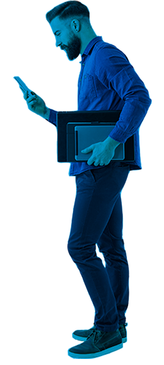 Man in blue color holding a laptop and looking at his mobile phone