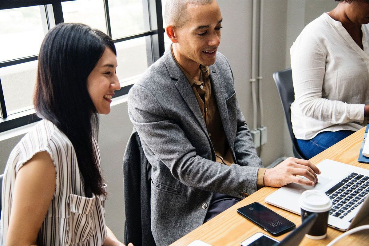 Man showing something to a girl on a laptop