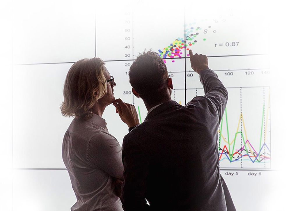 Two people discussing a graphic