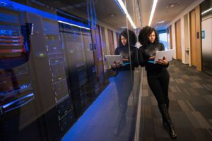 A woman with a laptop standing in a corridor