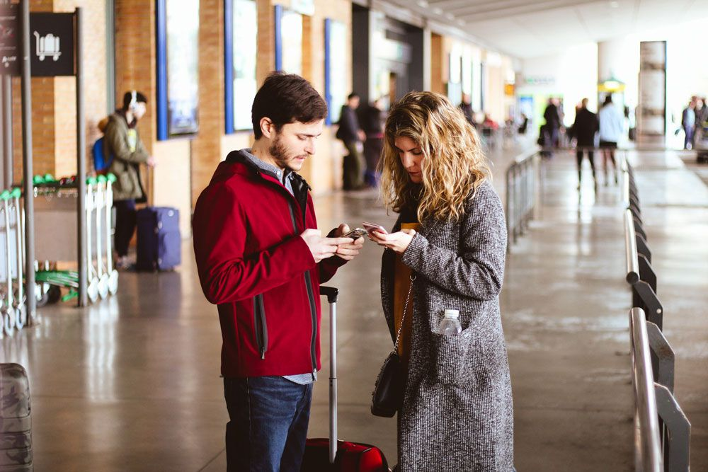 A man and a woman checking their mobile phones at an airport